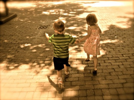 Little boy and girl skipping in walking mall