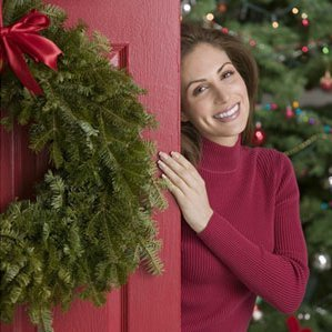 Stick to Your Holiday Budget: Entertaining, Holiday Entertainment, Woman Greeting Holiday Guests