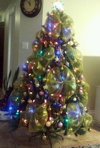 artificial christmas tree with lights decorations and large gold ribbon bows