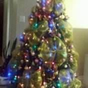 Artificial Christmas tree with lights, decorations, and large gold ribbon bows.