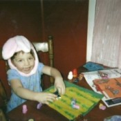 Child in bunny hat coloring.
