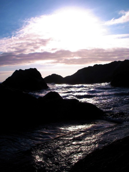 Sun shinning through clouds on rocky shore.