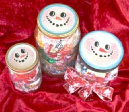 Jar lids decorated to look like snowmen.