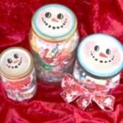 Jar lids decorated to look like snowmen.