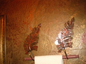 Copper colored leaf towel holder mounts.