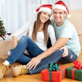 christmas ideas for men couple sitting on the floor wearing santa hats