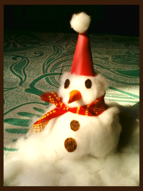 Finished snowman sitting on cotton snow.