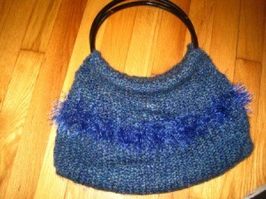 A purse that has been knitted from blue yarn.