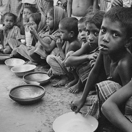 Hungry children sitting with empty bowls.
