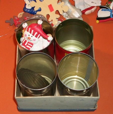 6x6 inch cardboard box holding 4 tin cans - one of which has a snoman ornament.