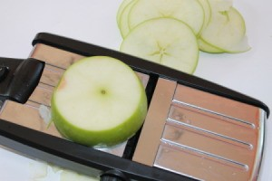 Cinnamon Apple Chips - An apple being sliced with a mandoline.