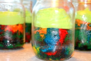 Rainbow cake with frosting, served in the mason jars.