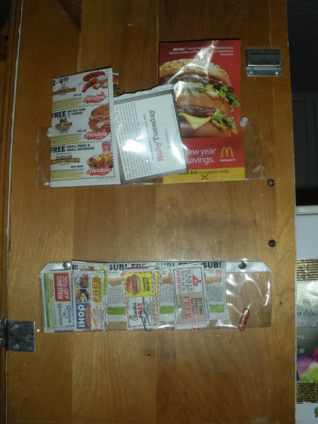 Organized restaurant coupons taped inside cabinet door