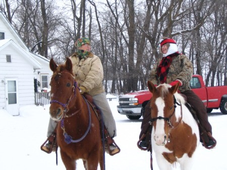 Two women riding horses in the snow.