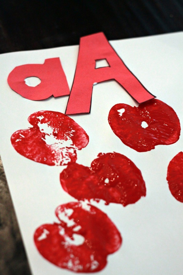 Capital A and Lower Case a on white paper surrounded by stamped apples