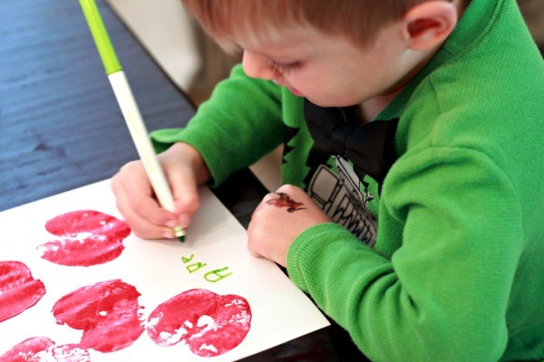 Young boy in green spelling apple