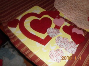 Adding felt heart cutouts to heart shaped framing piece..