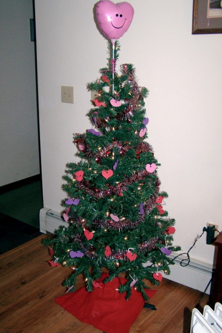 An evergreen tree decorated with hearts for Valentine's Day.