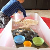 Child playing with dough in large storage bin.