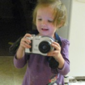 Give Old Camera To A Child, a toddler playing with an old camera.