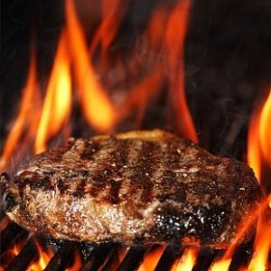 A steak being cooked on a grill.