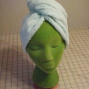 A turban towel on a green mannequin head