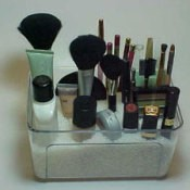Makeup brushes and tubes arranged in a container.