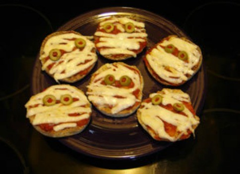 English muffin pizzas with strips of cheese and olive eyes.