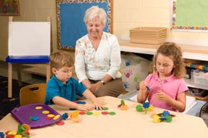 A grandma teach two younger children.