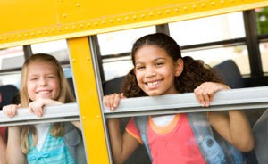 Two kids smiling out a school bus window.