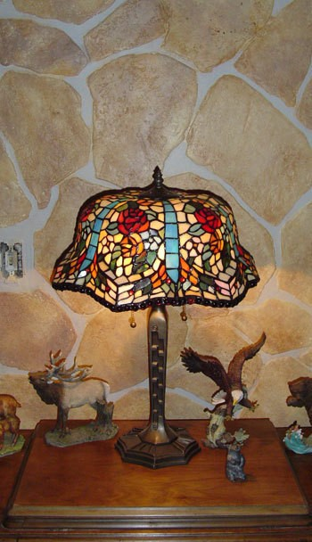 A faux rock wall behind a Tiffany lamp.