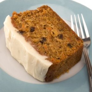 A piece of carrot cake on plate with cream cheese frosting