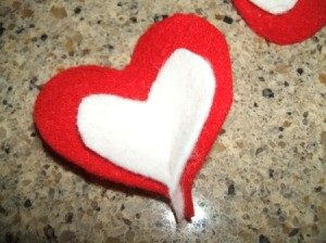 Pinching the tip of the glued hearts.