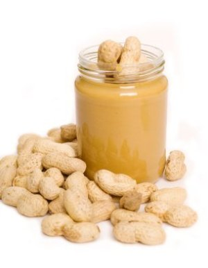 Jar of peanut butter surrounded by peanuts.