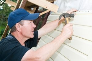 Saving Money on Home Repairs, Man Repairing the Siding on His Home