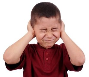 A child not listening by covering his ears.
