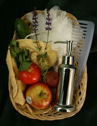 Basket full with apples, a cucumber, herbs, a soap dispenser, loofa, washcloth, and a comb.