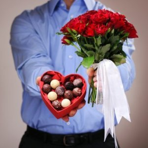 Valentine's Day Tips for Men, Man giving a heart shaped chocolate box and roses.