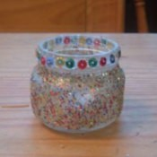 Candle holder made from a baby food jar and covered with glitter