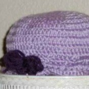 A purple crocheted hat for a toddler.