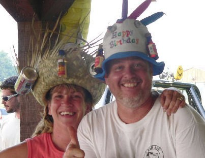 Two people with hillbilly survivor hats on.