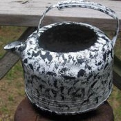 A teakettle that has been painted white and black.