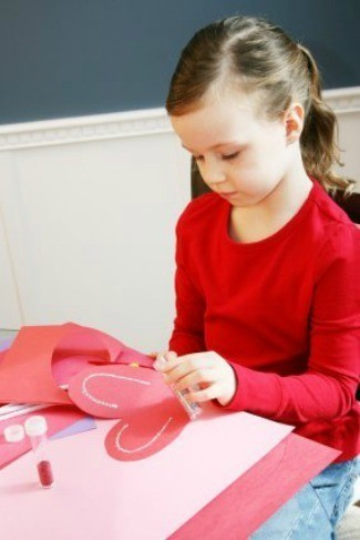 A Photo Of A Girl Making Paper Hearts