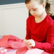 A photo of a girl making paper hearts.