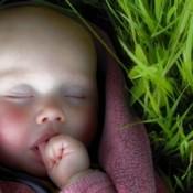 baby sleeping by grass
