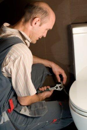 Man installing a toilet.