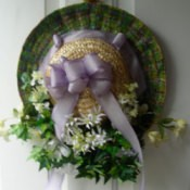 Straw hat decorated with flowers and greenery.