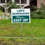 Recently seeded lawn with a keep off sign.