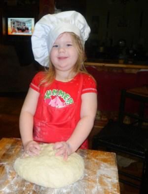 A little girl with a red apron and chef's hat kneading bread dough.