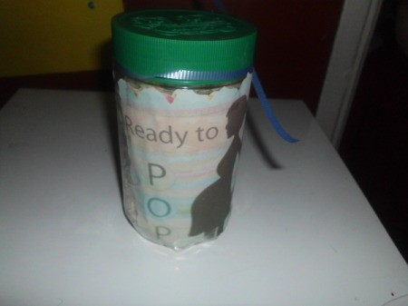 A plastic jar full of popcorn for a baby shower.